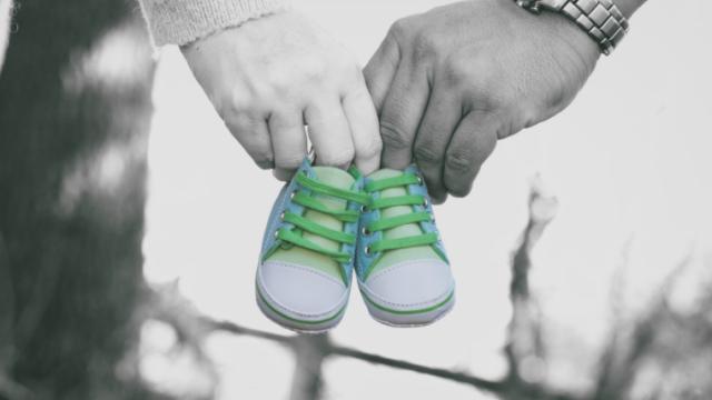 夫婦がこれから生まれる赤ちゃんの靴を持って歩いている